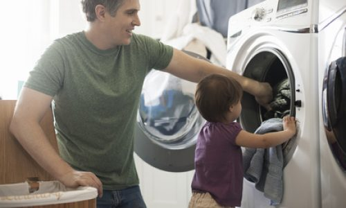 A man and a toddler empyting the laundry from the washing macine.